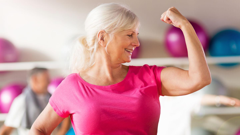 Eiweißmangel vermeiden: Frau mit weißen Haaren und pinkfarbenem Shirt lässt ihren Bizeps spielen.