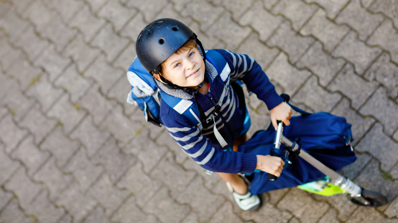 Mit Schnupfen in die Schule? Junge mit Schutzhelm hält Roller in der Hand.